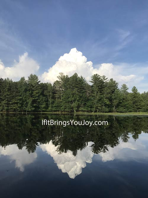 Clouds and trees reflecting on lake