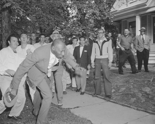 A reporter from the Tri-State Defender, Alex Wilson, is shoved by an angry mob of white people near Central High School in Little Rock, Ark., Sept. 23, 1957. The fight started when nine black students gained entrance to the school as the Army enforced integration. (AP Photo)