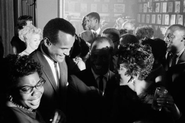 Gordon Parks captures Lorraine Hansberry chatting with Harry Belafonte (Sidney Poitier is in the rear and actor Godfrey Cambridge) at a party in honor of Ms. Hansberry's smash Broadway play, 'A Raisin in the Sun,' at Sardi's in New York City in March 1959. Photo: Gordon Parks/Time Life Pictures/Getty Images.