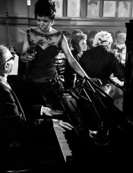 Lorraine Hansberry is captured by Gordon Parks chatting with the pianist at a party in honor of her play 'A Raisin in the Sun,' at the now legendary Manhattan restaurant, Sardi's in March 1959. Photo: Gordon Parks/Time Life Pictures/Getty Images