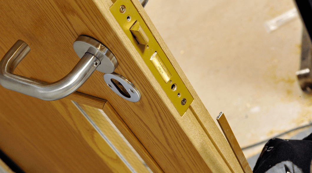 An intumescent seal in the process of being correctly fitted to the meeting edge of a double door leaf in accordance with the door suppliers instructions.
