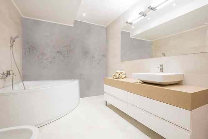 Neutral Bathroom With Mirrored Bath Panel And Tiles
