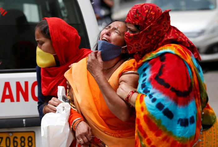 A woman is consoled after her husband died due to the coronavirus disease (COVID-19) outside a mortuary of a COVID-19 hospital in Ahmedabad, India, April 20, 2021. Source: newsindiatimes
