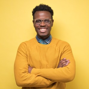 Smiling african american young man inyellow sweater smiling confident at camera.