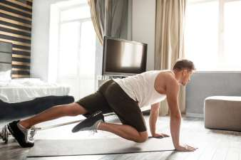 Young well-built man go in for sports in apartment. He stand on hands and move legs. Guy look straight forward. He exercise alone in room