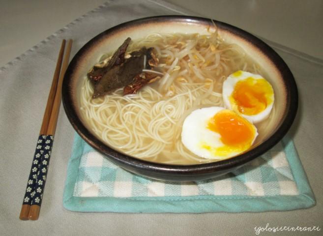 Ciotola di noodles giapponesi in brodo di miso e dashi con funghi, germogli di soia e uovo sodo