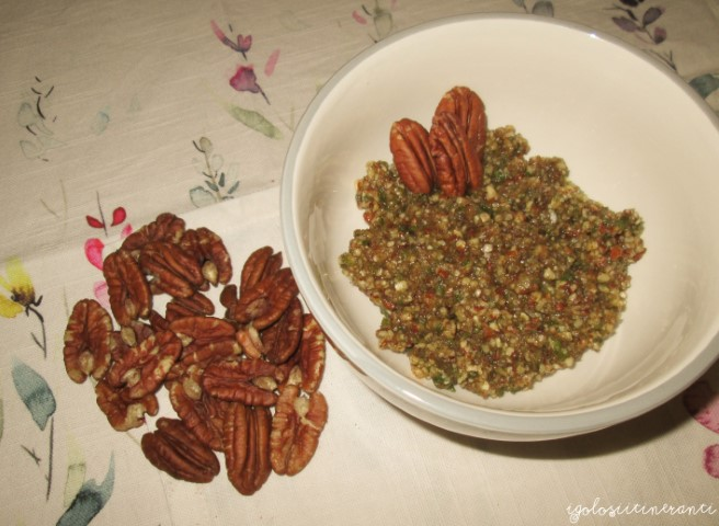 Ciotola di pesto alle noci pecan con accanto le noci intere