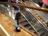 """Малышка машет """"пока"""" людям, которые спускаются вниз на эскалаторе"""