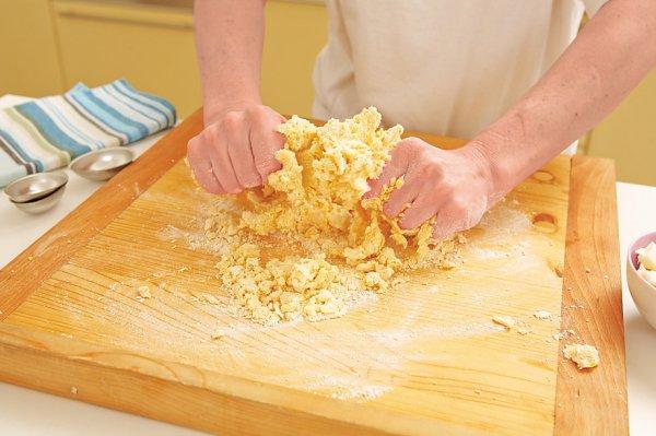 Яйца растираем с сахаром, добавляем мягкое масло и цедру лимона. Просеиваем муку горкой, проделываем углубление в горке и выливаем туда нашу смесь. Тесто смешиваем руками