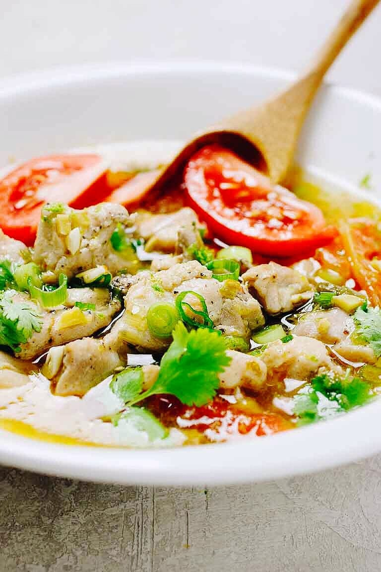 Paleo Chicken Pho Soup recipe with tomatoes, simmered with juicy chicken thighs and lemon and lime zest in a clear chicken broth.