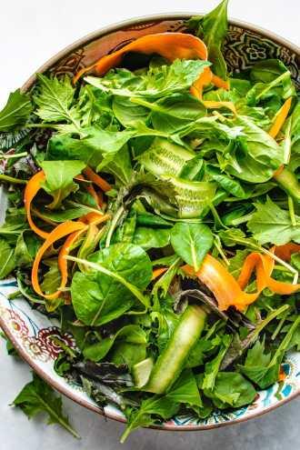 Photo shows a big bowl of fresh salad greens