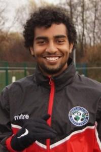 young smiling footballer in rain jacket