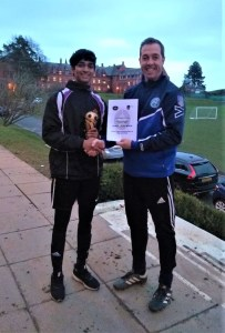 Young player receiving trophy from his coach, both smiling facing the camera