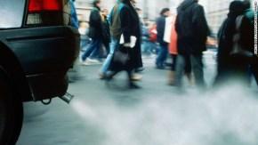 People walking on city street, car exhaust emitting smoke, low angle