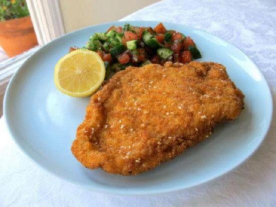 Подайте куриный шницель в панировке с салатом из свежих овощей и половинкой лимона