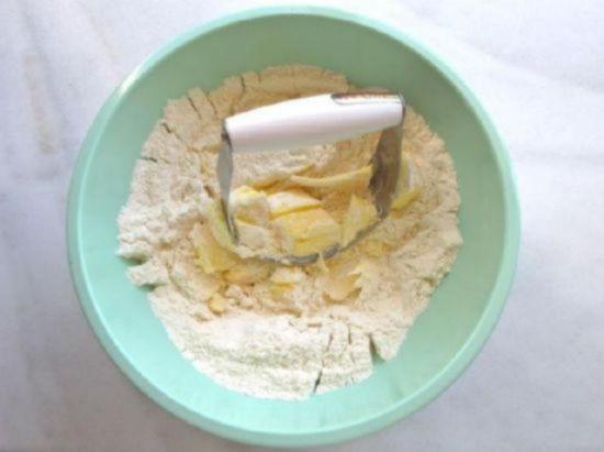 Кондитерским скребком рубите масло и вмешивайте его в муку