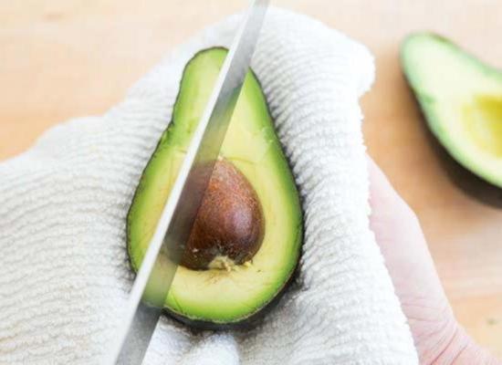 С небольшим усилием, аккуратно, вдавите лезвие ножа в косточку авокадо