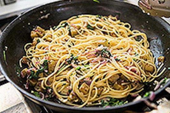 Смешайте в сковороде спагетти с баклажанами, обжаренным луком и зеленью