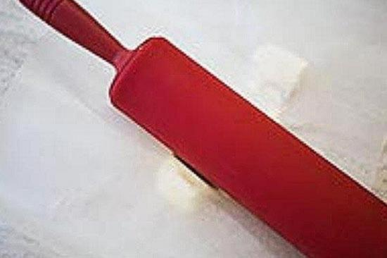 Положите сливочное масло между двумя листами вощенной бумаги и надавите на него скалкой