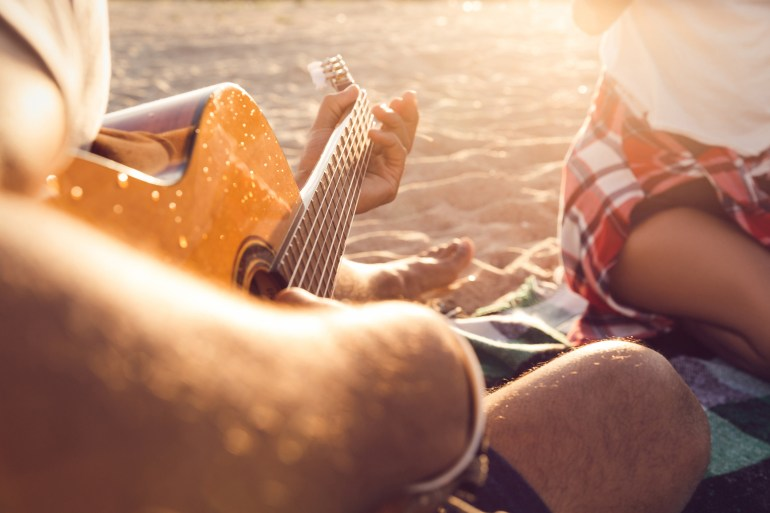 Cropped image of a guy playing guitar for his friends