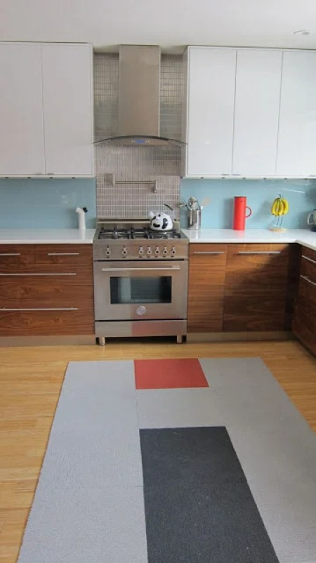 Retractable kitchen island covered by rug