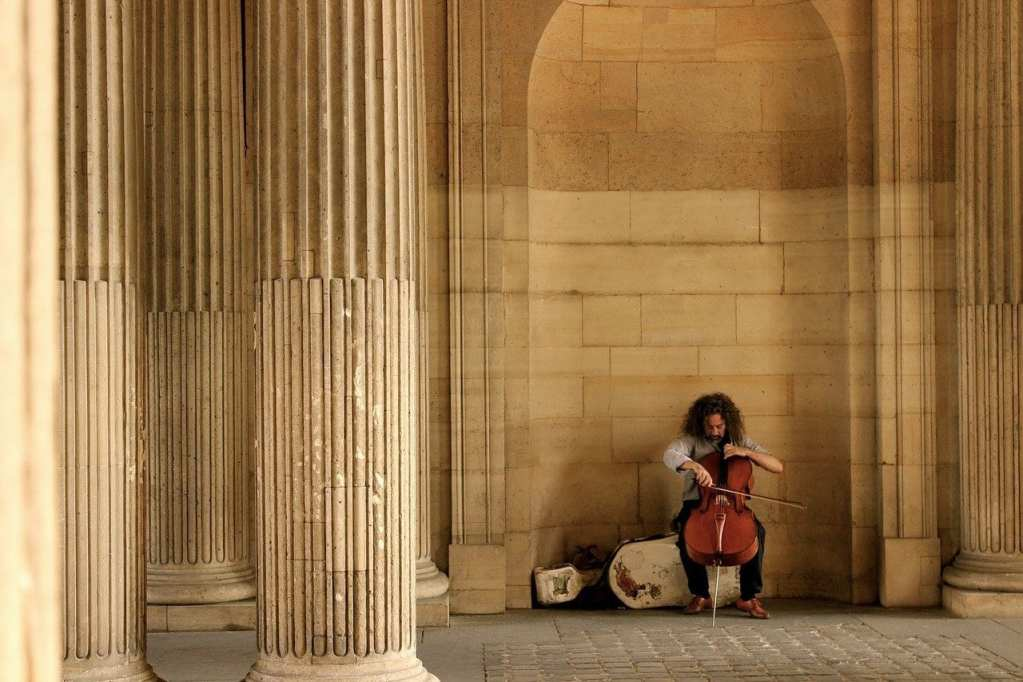 Cellist sitting in a nook in Paris, France