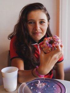 Libby Cladwell holding a sprinkled donut