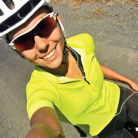 Catherine Colyn taking a selfie while wearing neon yellow bike kit