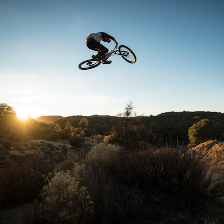 downhill bike racer Dillon Lemar catching air at sunrise