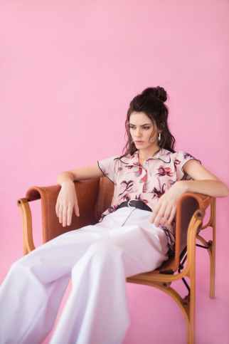 Picture of woman on chair pink background feeling Pre-menstrual PMS