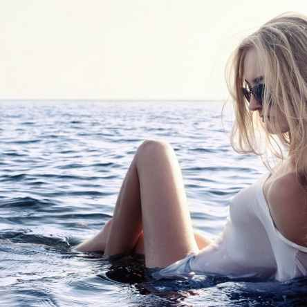 Divine Feminine Woman with blonde hair, white top and black sunshades