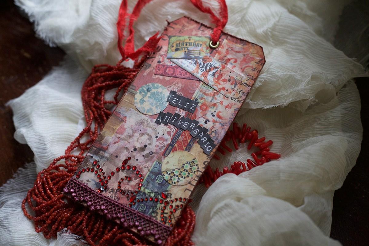 Tag de aniversário feito com colagem de vários papéis, renda e cristais