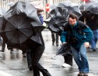 People fight against strong winds and rain