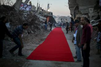 Palestinians place a red carpet between the ruins of houses, that witnesses said were destroyed by Israeli shelling during a 50-day war last summer, before they display a film on the war in the east of Gaza City May 12, 2015. REUTERS/Mohammed Salem