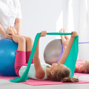 Energetic school girls exercising with resistance bands and balls with the help of an instructor