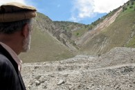 A man looking at a landslide occurred just hours before.