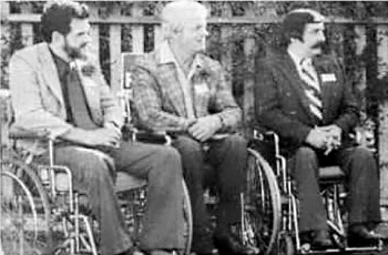 Black and white photo from 1976, with 3 men in wheelchairs, all wearing suits. Darrell McDaniel, Lou Nau and Bob Campbell. Co-Founders.