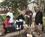 Clients with disabilities in the Training House garden. Two men in wheelchairs.