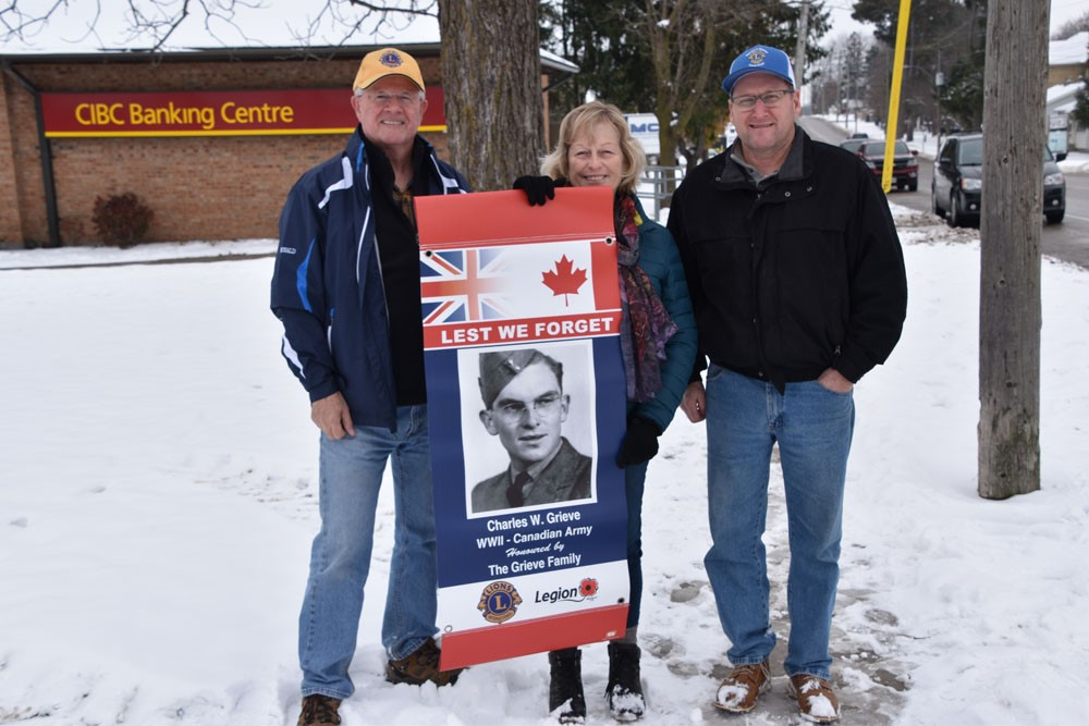 pictured is Lion Murray McDonald, Barb Mcinroy, Lion Ed Robb holding the remembrance banner