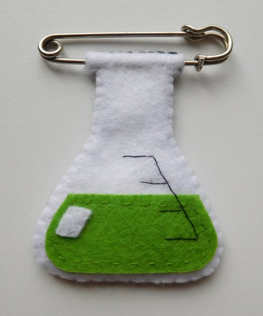 With green liquid, hung on oversized safety pin