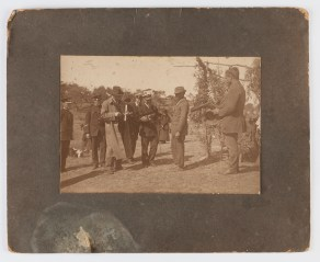 Jack and Wes Simms showing a boomerang to a naval officer