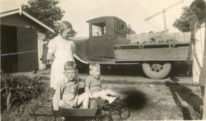 John Street at two and a half years of age with his brother Jim (four and a half). Their mother Gladys Ada is at the right with their father's old truck in the background - 1943