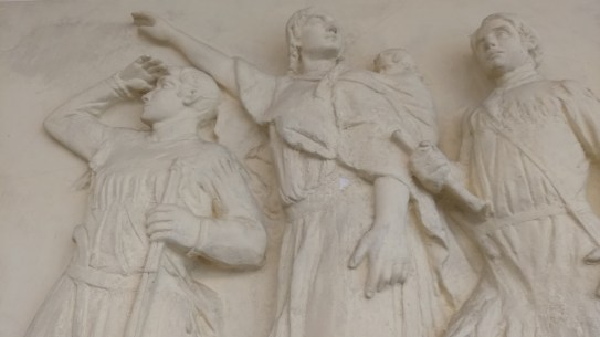 """A bas-relief, """"Sacagawea Leading Lewis and Clark to the Pacific Ocean,"""" adorns the wall of the library. The artist of the work is unknown."""