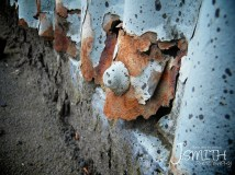 The edges of the Iron rusting, made brittle despite the attempts to protect it with paint.