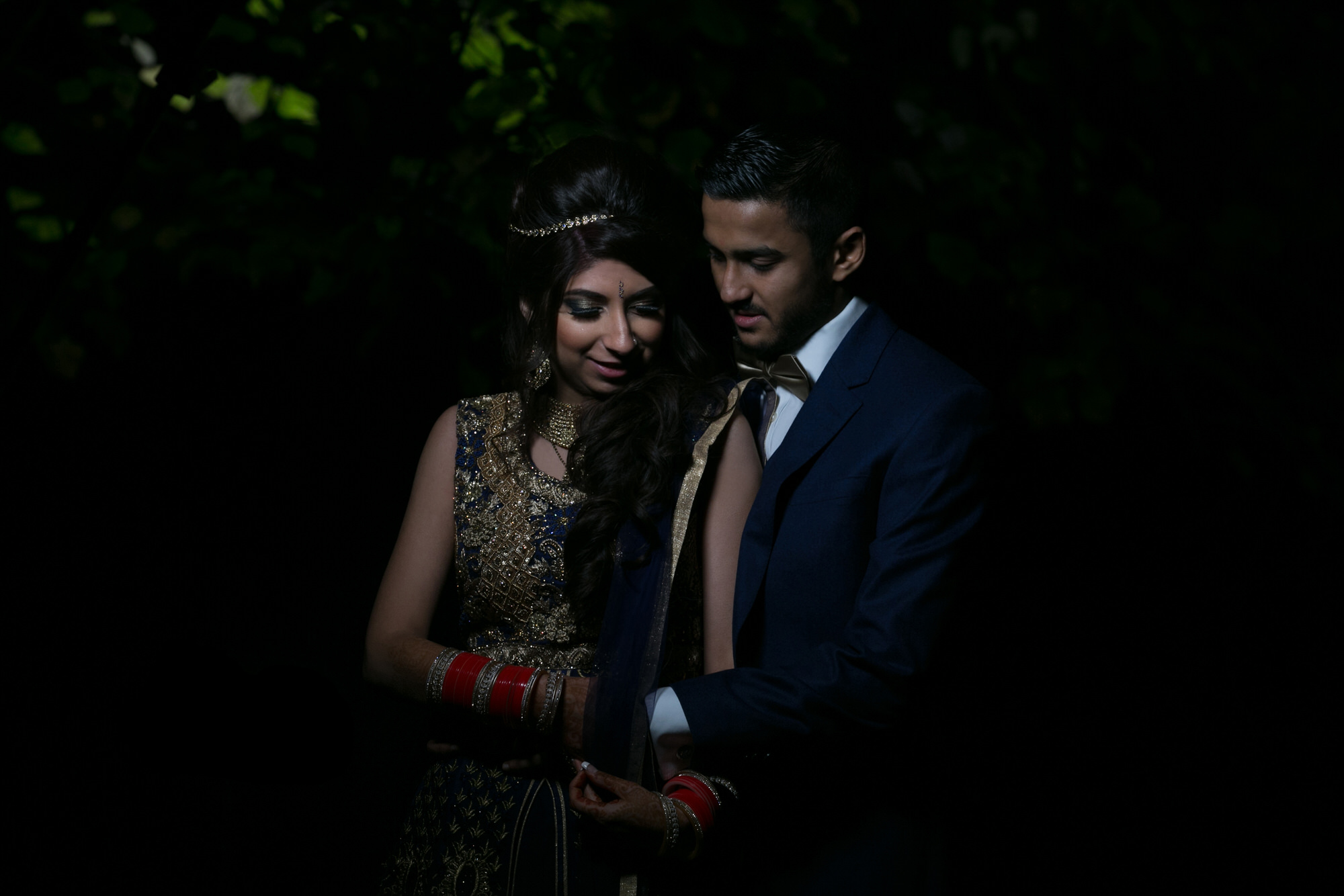 Indian couple wearing smart evening wear holding hands