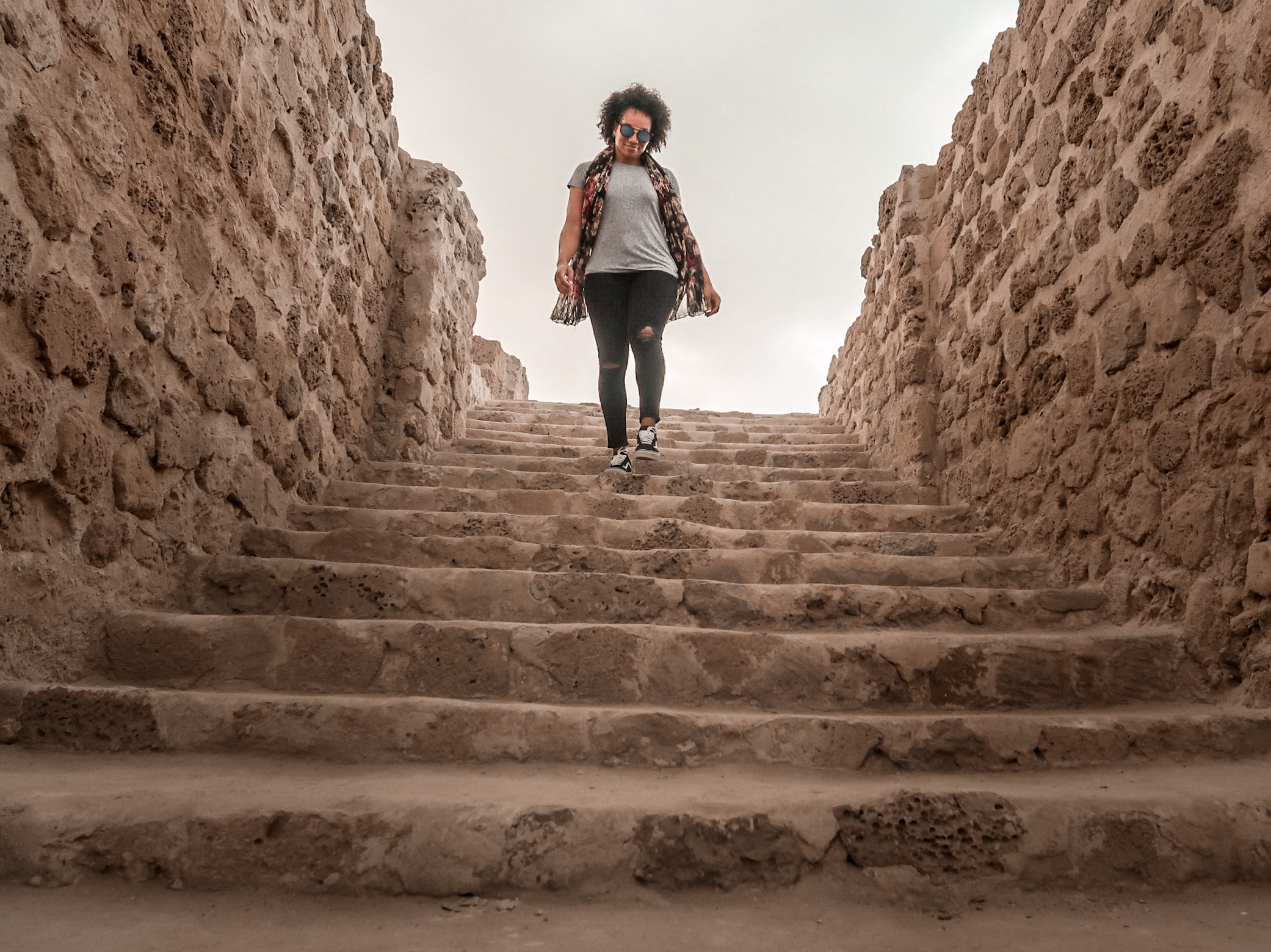 Illustrated by Sade - Woman walking down steps of archaeological site of the Bahrain Fort