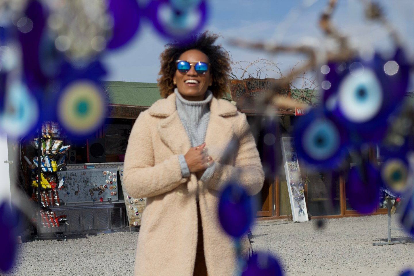 Illustrated by Sade - Taking a photo in front of a tree adorned with evil eye ornaments in Love Valley, Cappadocia