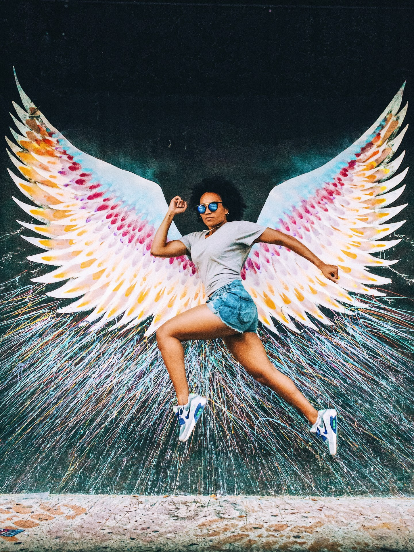 Illustrated by Sade - Woman taking a photo jumping in front of wings art graffiti mural in Wynwood Art District in Miami, Florida