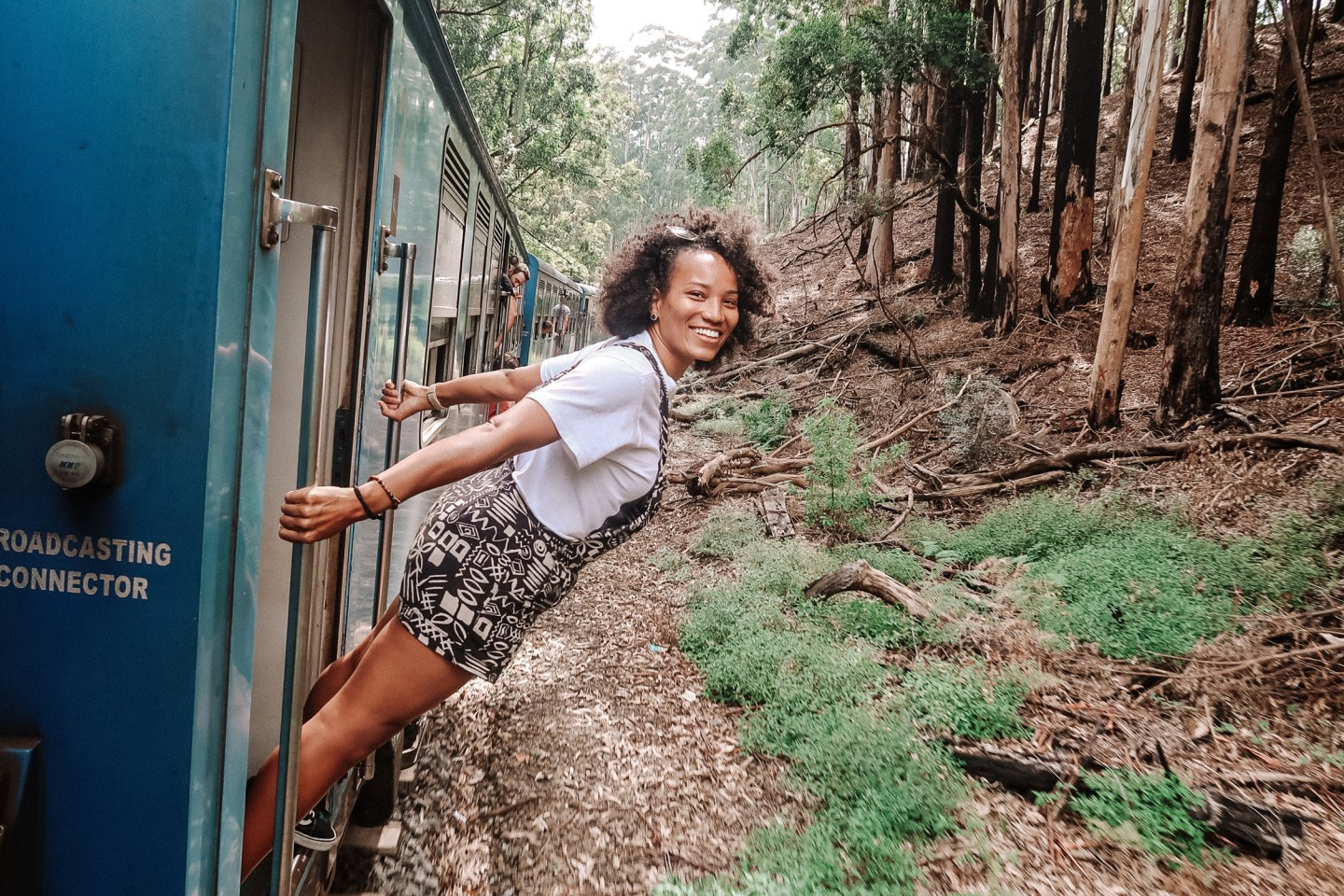 Illustrated by Sade - Solo female traveler taking photo on moving train from Kandy to Ella, Sri Lanka