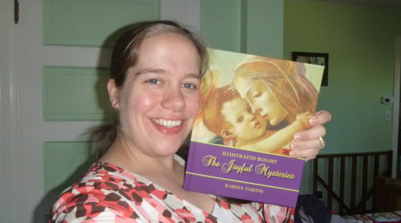 Karina Tabone holding up her first book, The Joyful Mysteries. Via IllustratedPrayer.com